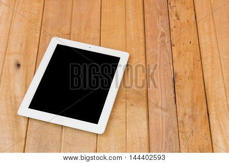Isolate white ipad on brown wood table background