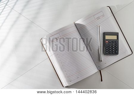 On The Table In An Open Diary And A Pen With A Calculator.
