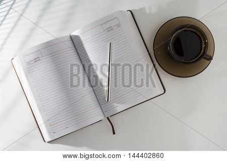 On The Table In An Open Diary And Pen, Standing Next To A Cup Of Coffee.