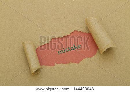 Mistake word under brown torn paper .