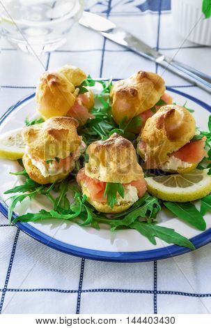 Cocktail snack. Finger food. Savory Pate a Choux (Savory Puffs) with Smoked Salmon and Goat Cheese