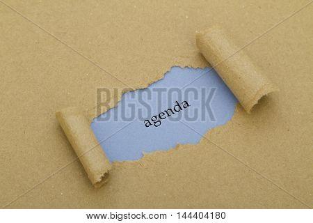 Agenda word written under torn paper .