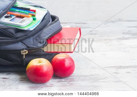 School backpack with supplies and apples on white wooden desktop