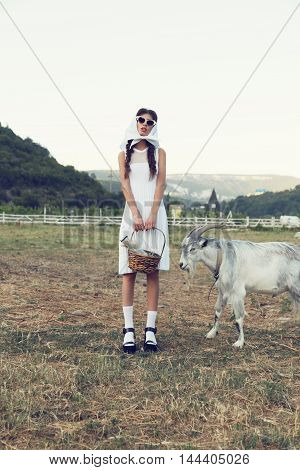 fashion photo of gorgeous sensual woman with dark hair and bright makeup, in elegant dress posing at farm with goat