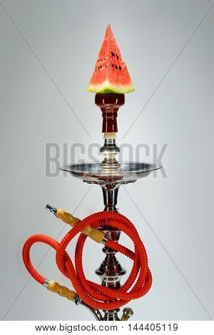 Smoking hookah with fruit tray on dark background