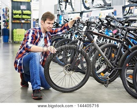 Man Checks Bike Before Buying In Shop