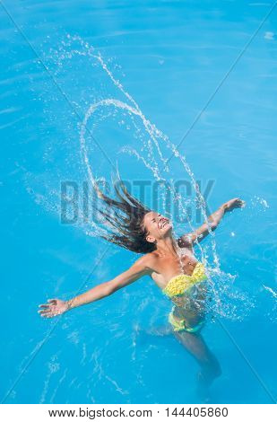 young woman doing a spin with her hair in the pool