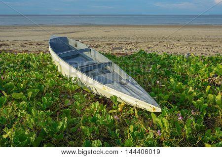 The fisherman boat on the Manikar tropical beach Labuan island with tropical flowers at Labuan Pearl Of Borneo,Malaysia.