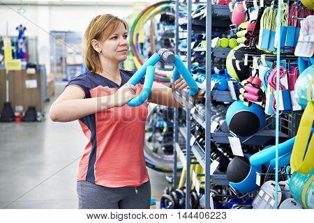 Woman Chooses Sport Equipment