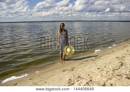 Young beautiful girl with straw hat standing and look on the side in the blue sea near the yellow sand