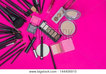 Cosmetics and makeup brushes on pink background with copy space.