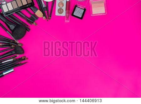 Cosmetics And Makeup Brushes On Pink Background