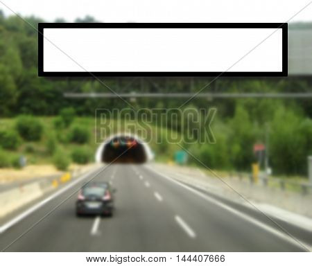 Billboard with blank advertising panel screen in a middle of a highway blurred background