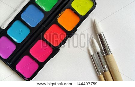 Bright color paints and  brushes on paper background