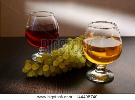 red and white wine in the glass is on the table, along with grapes