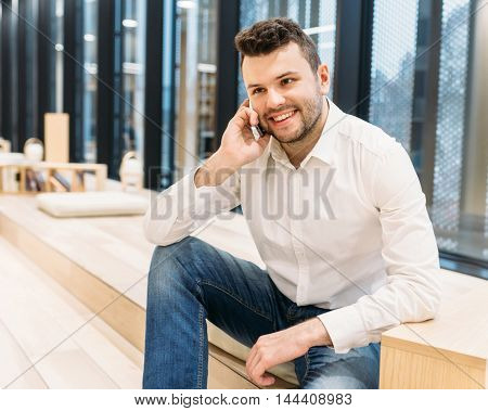 Young businessman talks on the phone modern office communication management