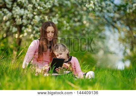 Mom with her daughter and tablet computer in nature