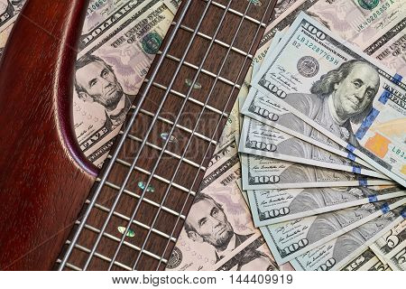 Still life guitar with dollars as a background. Music and money concept, closeup, top view.