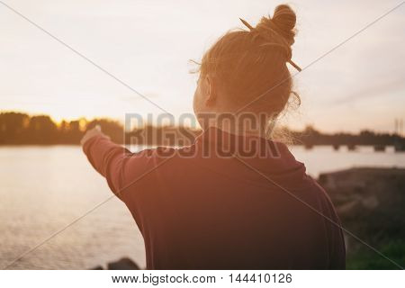 portrait of teenage girl on embankment in sunset, toned photo