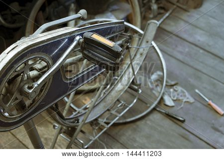 Repair of a broken bicycle standing upside down in a garage or workshop indoors filtered shot