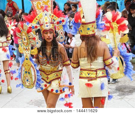 Cajamarca Peru - February 8 2016: Young women in colorful feathered costumes dance in Carnival parade in Cajamarca Peru on February 8 2016