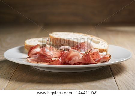 speck slices on white plate with ciabatta on old wood table, shallow focus