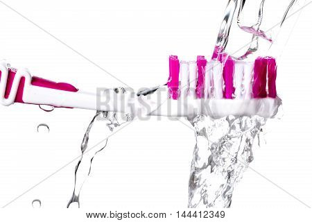 Toothbrush under splashing water isolated on white background closeup.