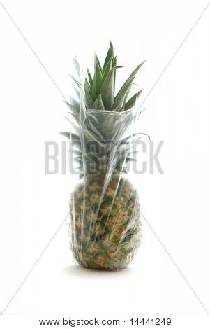 Pineapple in a plastic bag isolated on white