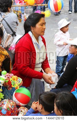 Cajamarca Peru - February 8 2016: Andean woman with red sweater sells toys during Carnival parade in Cajamarca Peru on February 8 2016