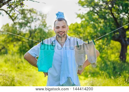 man near the children's clothing hanging on a rope outdoors