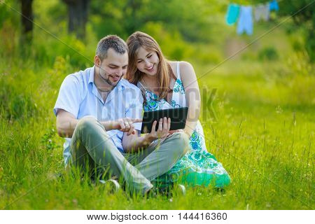 Happy pregnant couple with tablet on nature