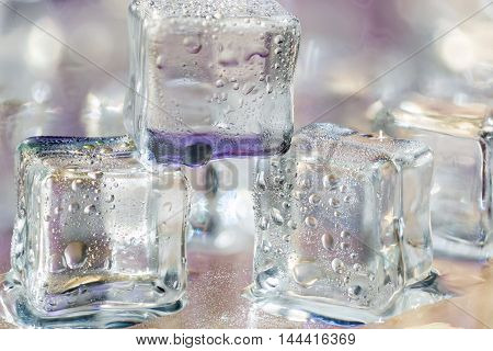 Melting transparent ice cubes on wet glass