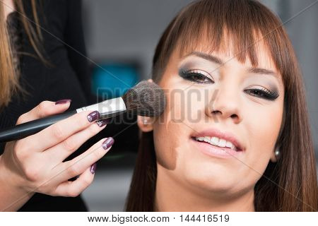 Make-up artist applying blush, toned image, close up