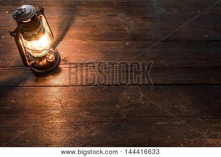 Olld-fashioned kerosene lamp on the dark table in twilight. Soft focus
