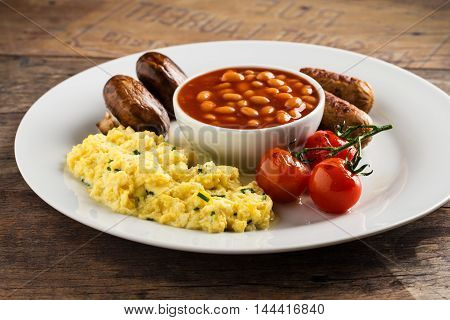 Breakfast with sausages scrambled eggs baked beans mushrooms and tomatoes.