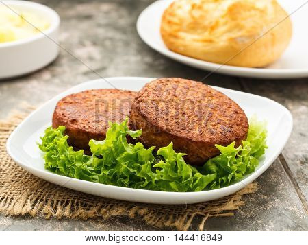 two vegetarian burgers and potato bun and salad.