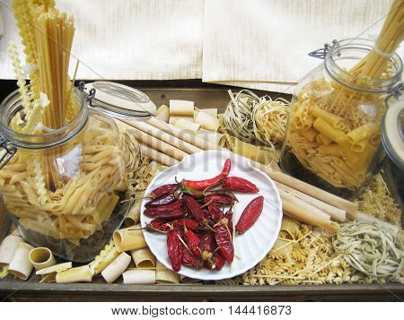 Different types of pasta and red pepper for cooking on a display