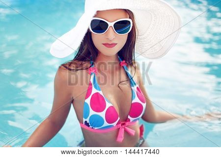 Woman in bikini hat and glasses relax in pool