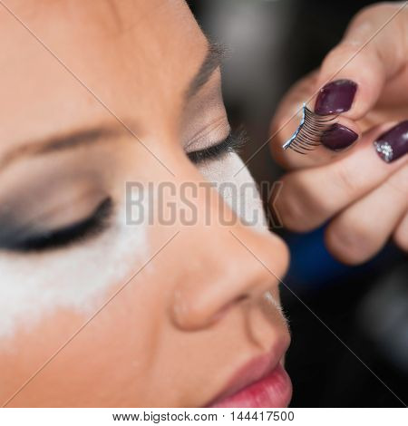 Makeup artist applying false eyelashes, toned image