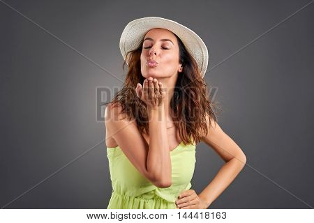 A beautiful young woman blowing a kiss in a green dress and a hat