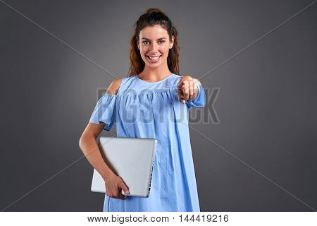 A beautiful young woman smiling and pointing in to the camera while holding a laptop in her hands.