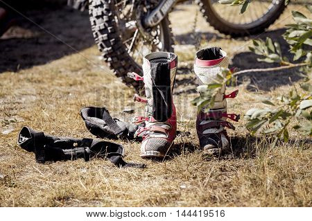 motorcycle racing boots and racer gloves after competition Enduro