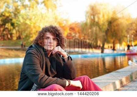 Young hot man autumn portrait, take a restin park against lake