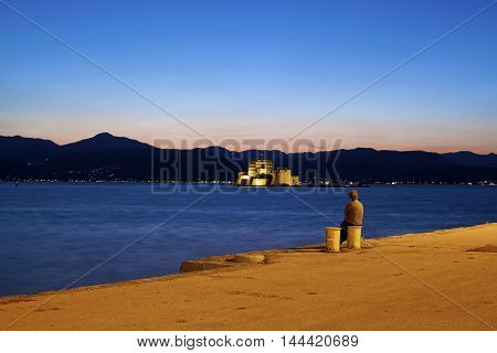 Lonely elder lady sitting on the dock
