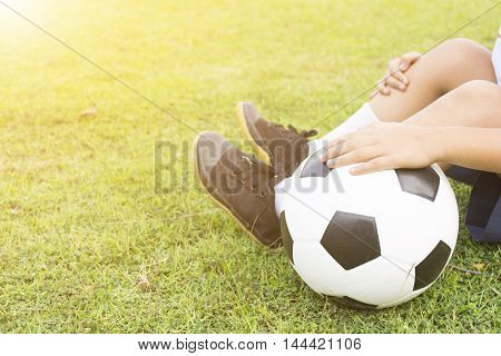 Boy is sitting on green grass with a soccer ball in his hand.Close up