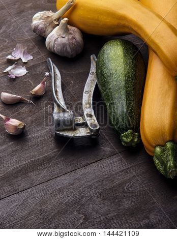 Garlic and galic crusher and three zuccini two yellow and green.Wooden background.Vertical shot.Free space