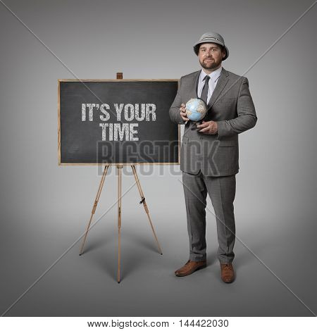 Its your time text on blackboard with businessman holding globe in hands