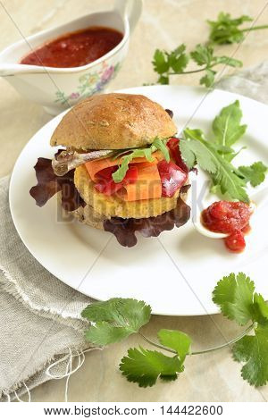 Vegetarian bean burgers with vegetables served with sauce, vertical
