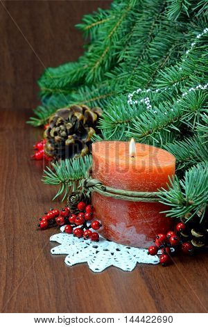 Christmas in a village house. Burning candle cedar conesred berries tree. Celebration atmosphere.Decorated tree branch on wooden background.