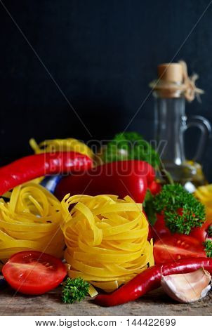 raw pasta with tomatoes and peppers on a black background
